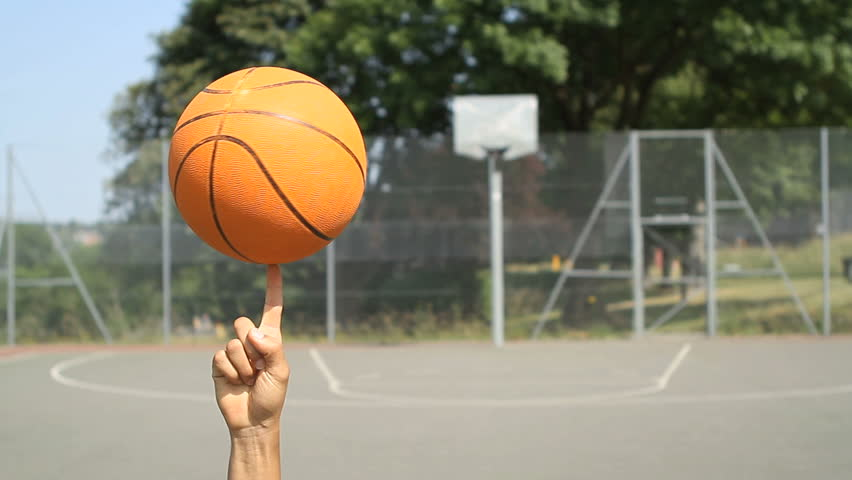 Basketball balancing and spinning on a finger on an outdoor basketball court #5039219