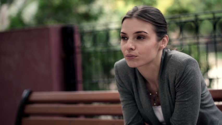 Sad, depressed beautiful woman sitting on bench in park