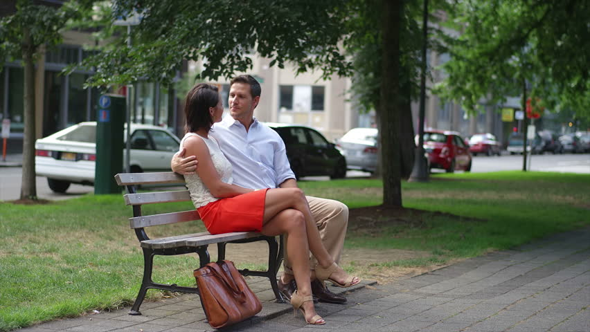 A couple takes a seat on a park bench in the city during the day | Shutterstock HD Video #5054366