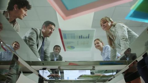 Team of business people with manager and colleagues talking during corporate presentation in meeting room, looking at documents and charts on table. 12of20