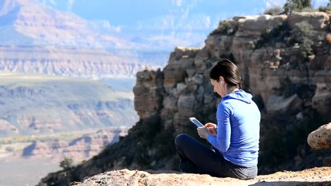 Woman using a phone in the mountains outside Zion National Park in the desert of southern Utah.