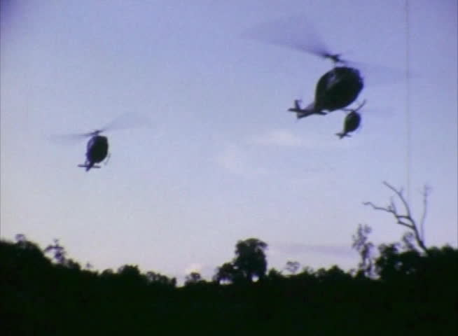 U.S. Army helicopters coming in for a landing at an First Cavalry infantry base during the Vietnam War. Vintage Super 8 footage.