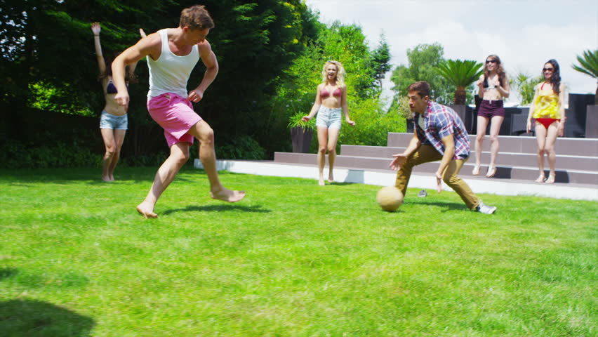 Athletic group of young male friends play soccer in the garden of contemporary home in the summertime. In slow motion.