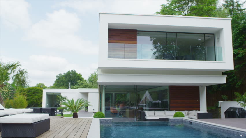 View of the exterior of a luxury contemporary home with swimming pool and lush green garden. No people.