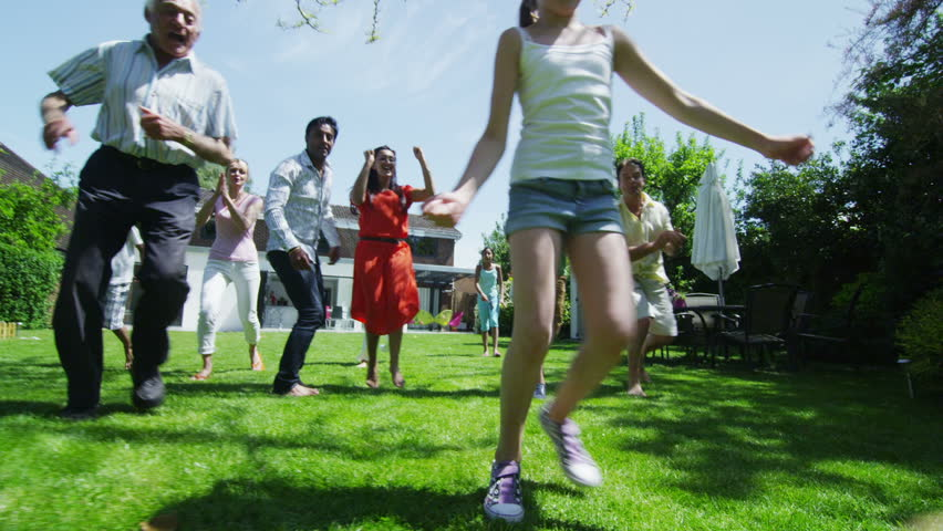 Happy mixed ethnicity group of friends and family with many generations, playing sports and having fun in the garden on a summer day. In slow motion. #5131808
