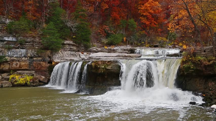 Whitewater spills off a rocky cliff  surrounded by woods full of fall foliage color at Upper Cataract Falls, a waterfall in Indiana.