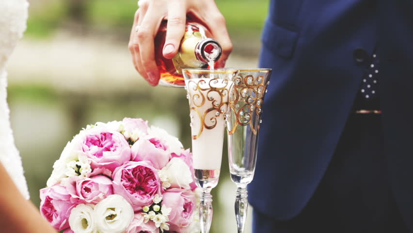 Groom pours champagne glasses clink glasses and the newlyweds, FullHD