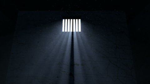 A slow pan of an empty dark jail cell with light rays penetrating a barred window