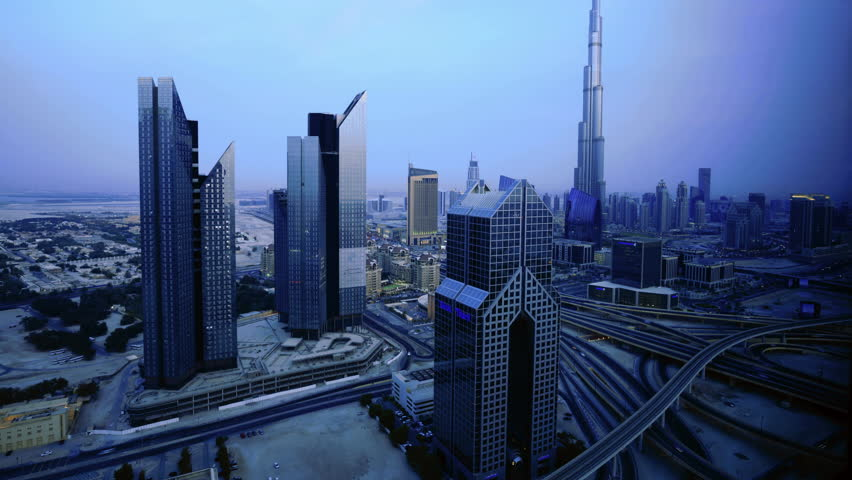 Dubai cityscape, dusk to night transition time lapse. high angle view looking towards Burj Khalifa and Business District towers.