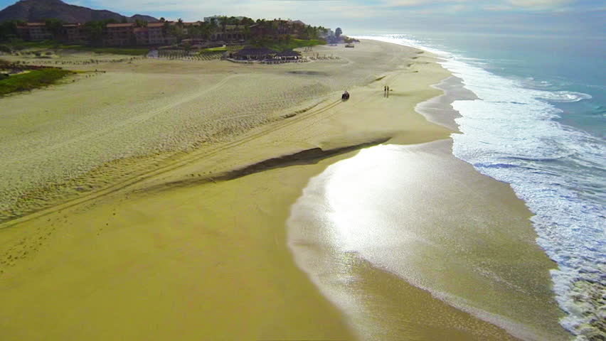 Aerial view of ATV driving down a beautiful wide open beach with crashing ocean waves