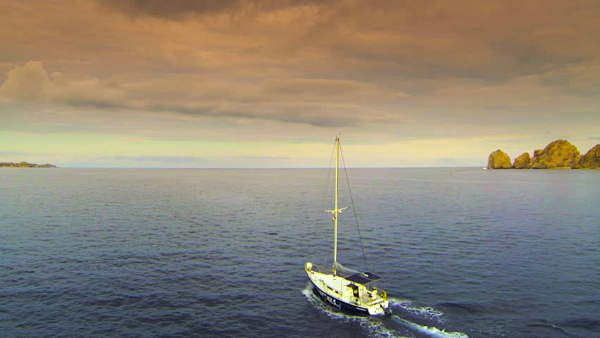 Sailboat aerial chase on the ocean at sunset on the sea of cortez in Cabo San Lucas Mexico