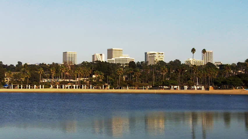 Shot of high rise office buildings from across a lagoon in Newport Beach, California. This long shot of the buildings in the distance look like an affluent and prosperous metropolis oasis.