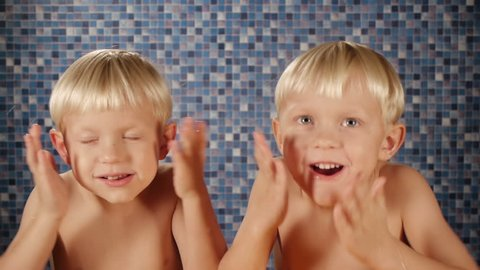 blond twin brothers using after shave cologne in bathroom