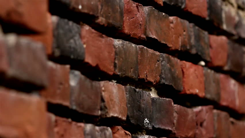 Some bricks on the wall are darkened to the point it is about to turn to black.