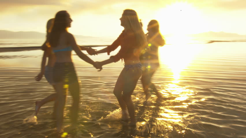 Group of Five Teenage Girls Dancing In The Water At The Beach At Sunset