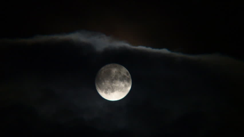 Time lapse of full moon emerging from behind night clouds.