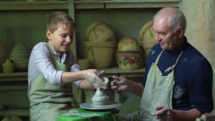Schoolboy making his first attempt to shape a clay vase at the pottery with the help of an elderly master