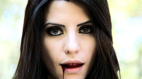 Beautiful female vampire tasting blood