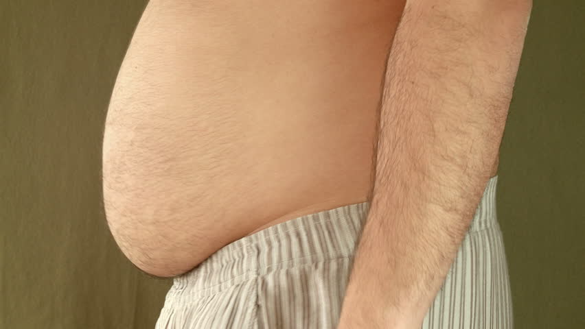 Man Playnig with his fat belly. Young Adult in pijama pants shakes his fat belly. Side shot.
