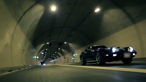 Blue car crosses the road in a tunnel