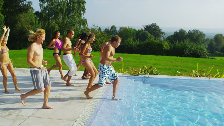 Happy fun loving group of friends running, jumping and diving into swimming pool at a pool party. In slow motion.