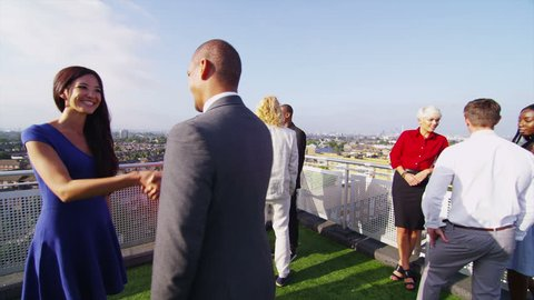 Smartly dressed group of friends or business colleagues chatting outdoors on a rooftop terrace overlooking the city. One man and woman meet and shake hands.