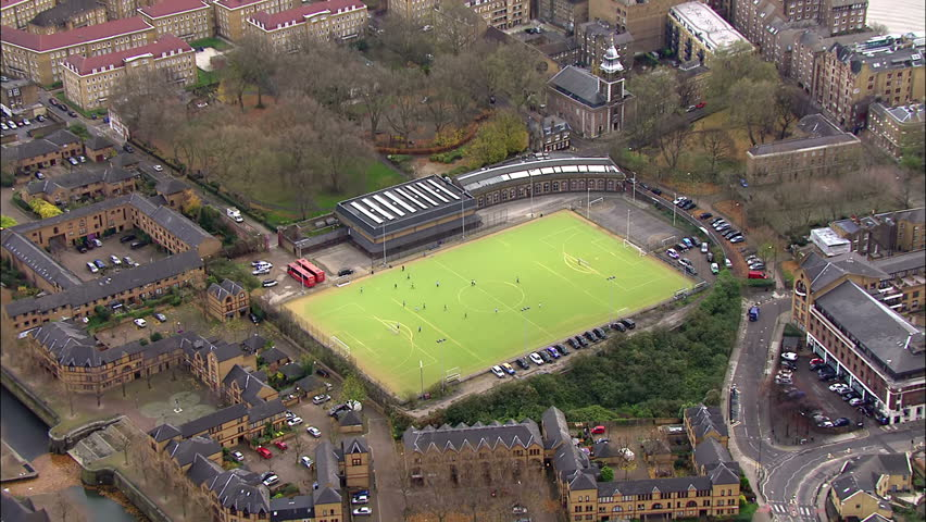 Aerial view above players on a soccer field in an urban area of London, UK.