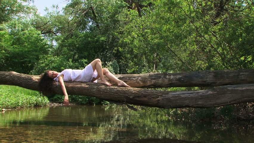 Woman resting in a forest on a riverside. In a forest.