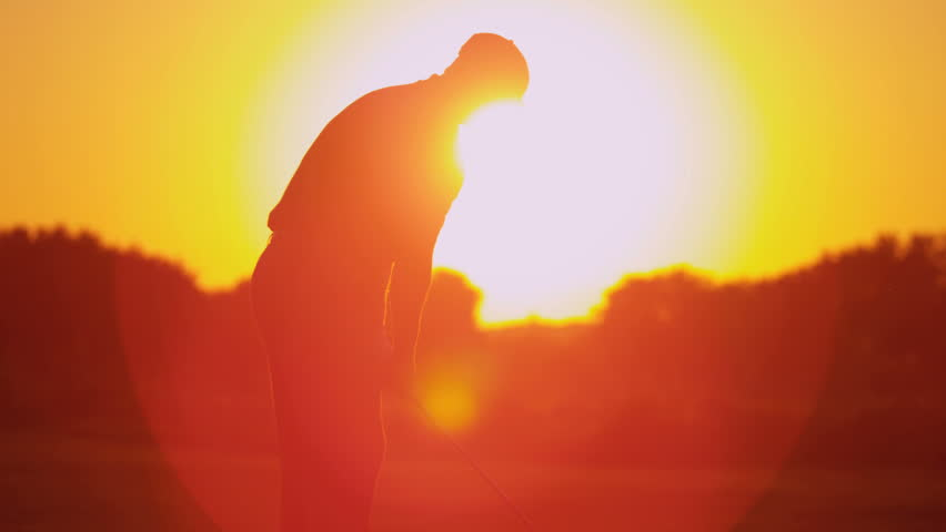Upper body male golf professional practicing his swing on green before teeing off in silhouette sunset shot on RED EPIC, 4K, UHD, Ultra HD resolution | Shutterstock HD Video #5337608