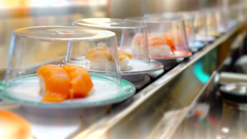 Sushi and Sashimi. Dishes of Sushi and Sashimi rolling on conveyer belt. Shallow depth of field. Blurred movement in the background.