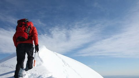 Mountaineer reaches the summit of a snowy ridge and expresses his joy - low angle view - HD1080p Canon 5DMkII