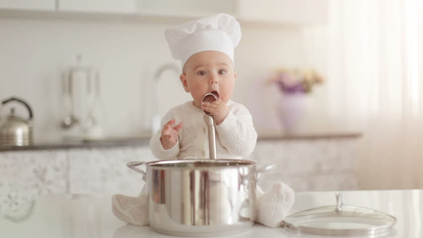 Baby sitting on table and eatting out of pan. Lens flare and sunlight | Shutterstock HD Video #5367899