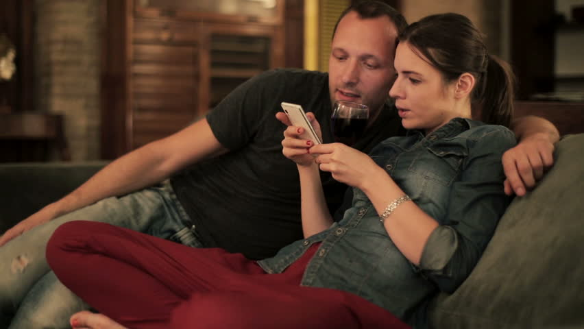 Young couple watching something funny on smartphone at home