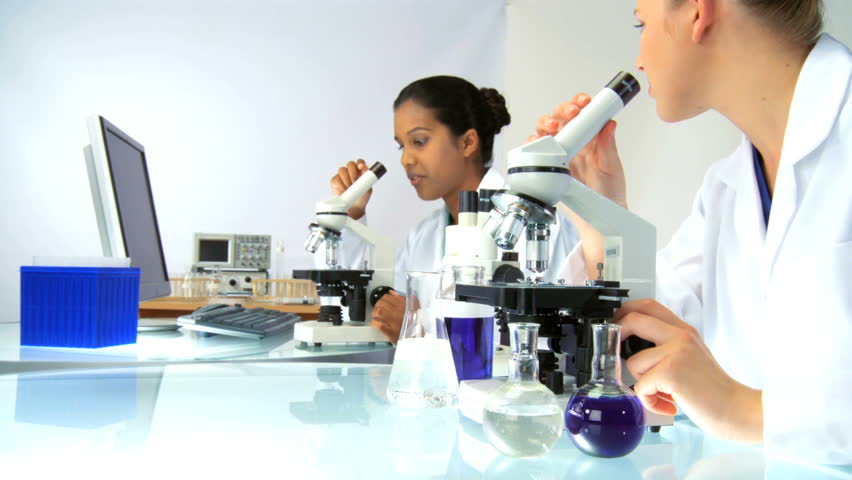 Female scientists in laboratory looking through a microscope