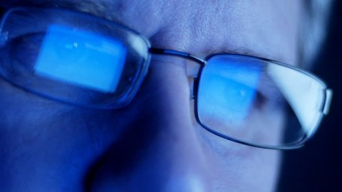 Computer screen and code reflected in man's glasses
