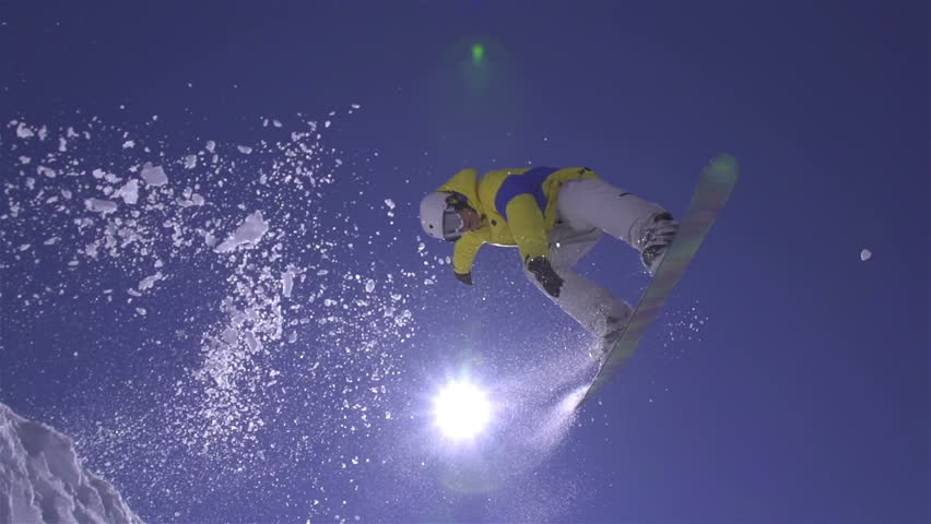 SLOW MOTION: Snowboarder jumps the kicker