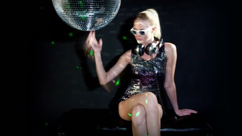 a sexy gogo dancer shot in a studio dancing and posing with a spinning disco ball. close crop on the face wearing cool sunglasses