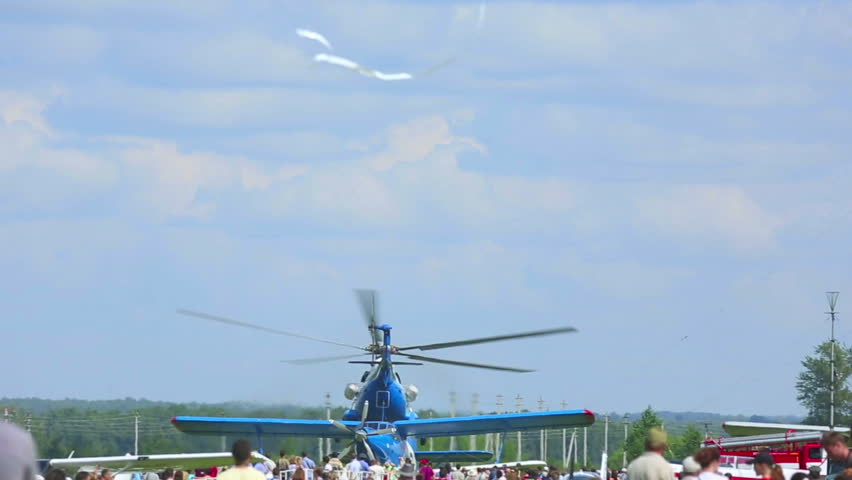 NOVOSIBIRSK, RUSSIA - JULY 28, 2013: People watching helicopter ascending at the airshow, celebration of Aviator's day airshow on July 28, 2013 in Mochishe airdrome, Novosibirsk, Russia.