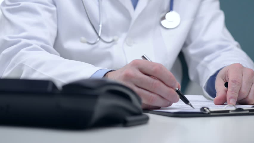 Doctor writing medical notes and answering phone calls.