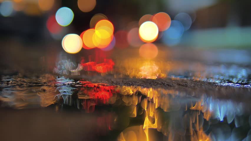 Colorful traffic lights bokeh circles blur reflecting in water on night city street road. Abstract background.