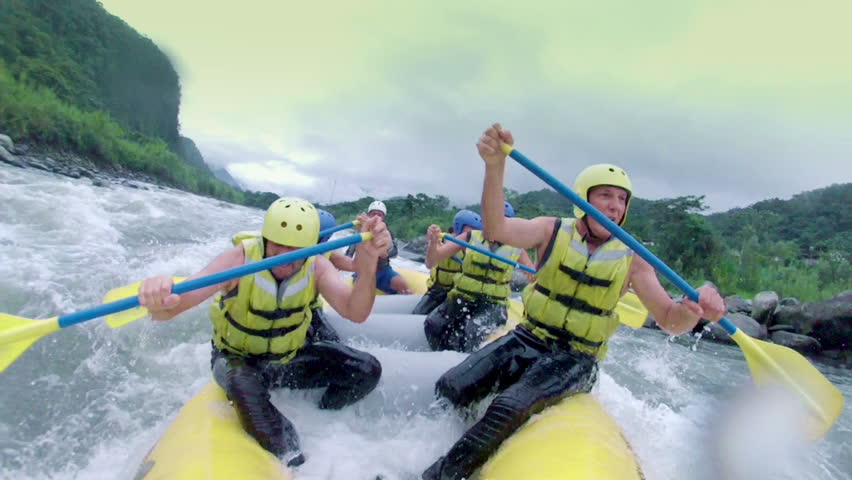 Team of six adult people white water rafting. On...