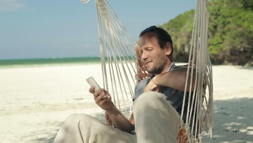 Young man on hammock using smartphone on beautiful exotic beach