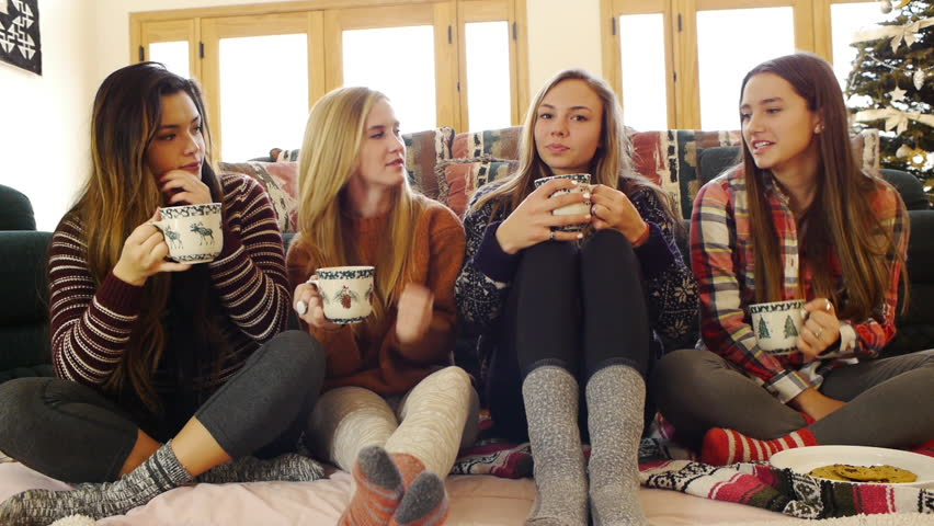 Multi Ethnic Group Of Teen Girls Clink Drink Hot Chocolate From Holiday Mugs