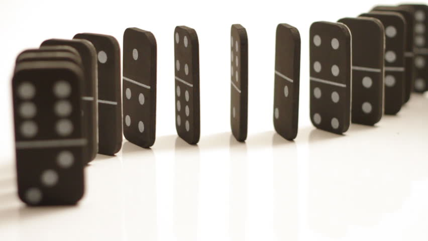 A curved set of black dominoes isolated on white, falling over, starting at the back and falling forward.