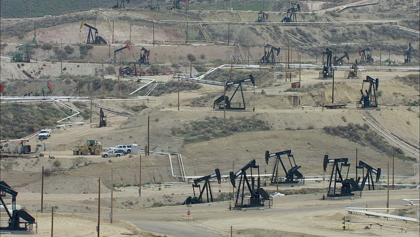 Oil Rigs Dirt Roads Hills. The shot shows oil wells extending for miles. The oil fields are comprised of hilly dirt roads and barren land. The rigs actively drill and extract oil from the wells.