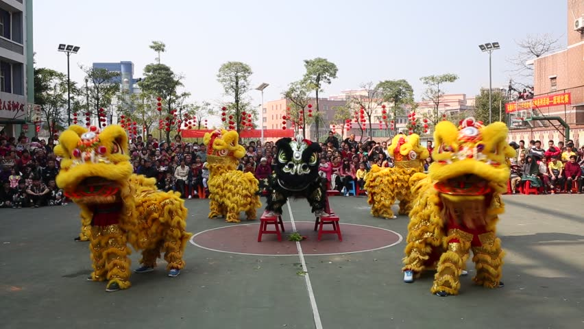 CHINA - JAN 31, 2014: Chinese new year day. Lion dance at a small town in south China. With every new year's coming, Chinese play traditional Chinese lion dance outdoor to celebrate and make wish.