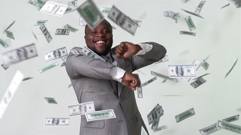 Slow-motion of an African-American businessman dancing among falling dollar bills in slow motion