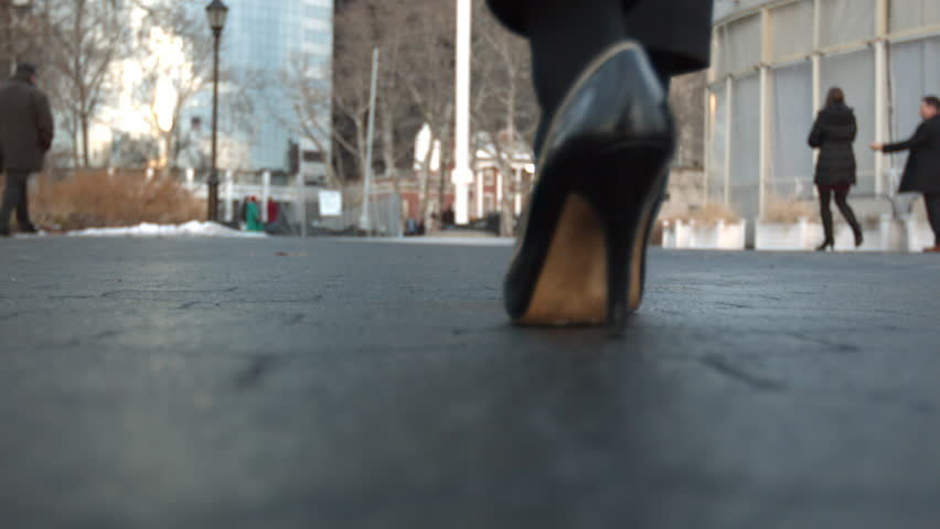 A slow motion video of a woman in high heels walking down a sidewalk with other commuters in New York City