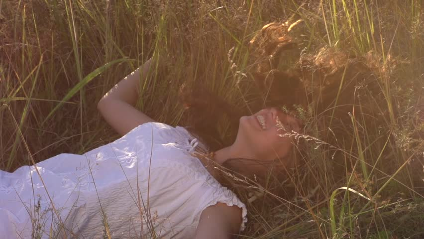 Beauty Girl with Healthy Long Hair Outdoors. Happy Smiling Young Woman falling down on the grass. Beautiful young woman lying on the field. Enjoying Nature. Slow motion video footage. Slowmo 240fps