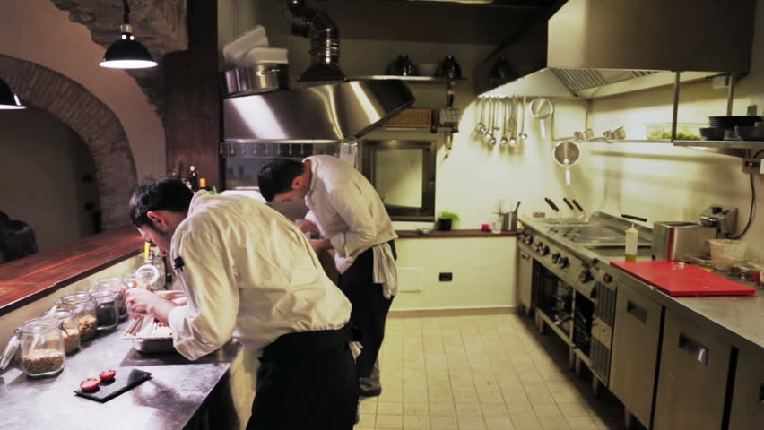 Restaurant Kitchen Chefs couple of male chefs clean the steel table and in restaurant